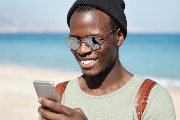 Tecnologia moderna, stile di vita, viaggi e turismo. messaggio di testo di battitura a macchina felice del viaggiatore maschio afroamericano sullo smartphone, esaminante schermo con l'ampio sorriso durante la passeggiata alla spiaggia il giorno di estate soleggiato