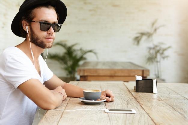 Tecnologia umana e moderna. moda giovane uomo barbuto che indossa un cappello elegante e sfumature nere rilassante al bar con terrazza, seduto al tavolo con la tazza