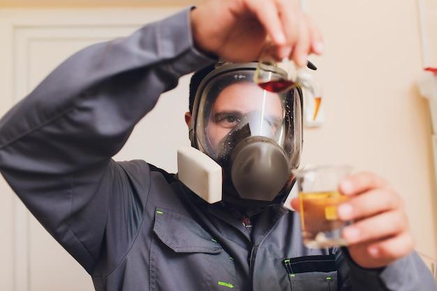Tecnologo in tuta protettiva bianca con retina per capelli e maschera che lavora nella fabbrica di alimenti e bevande. specialista dell'uomo che controlla le bottiglie per produzione di bevande.