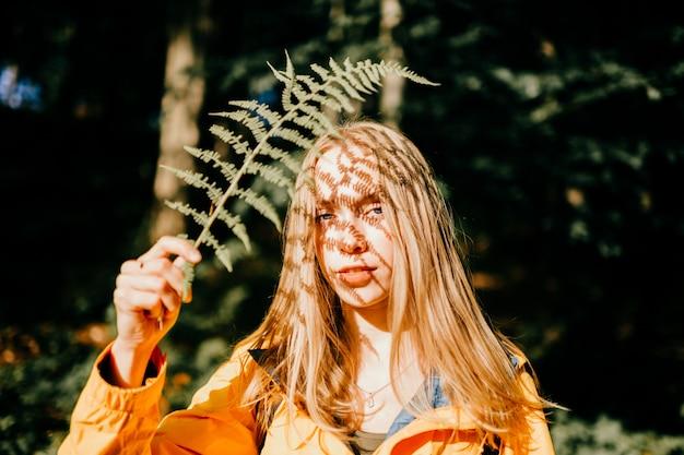 Teen affascinante con bella ombra modello dalla luce del sole che cade sul suo viso attraverso il ramo di felce