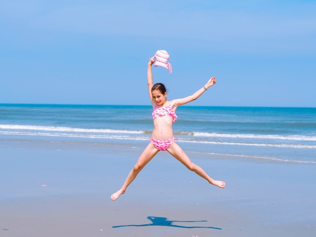 Teen ragazza divertirsi sulla spiaggia tropicale e saltare in aria sulla costa del mare