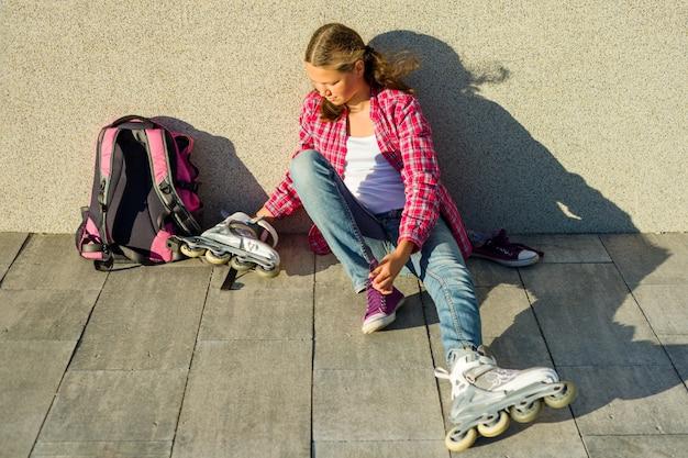 Teen ragazza rimuove scarpe da ginnastica e pattini a rotelle vestiti