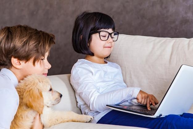 Teen ragazzo e bambina con cane guardando portatile