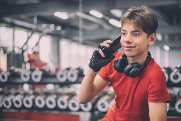 Teenager impegnato in un fitness club parlando al telefono