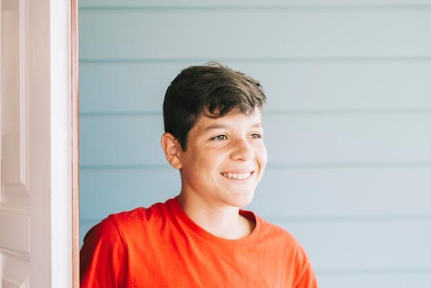 Teenager maschio sorridente che sta all'aperto mentre distogliendo lo sguardo