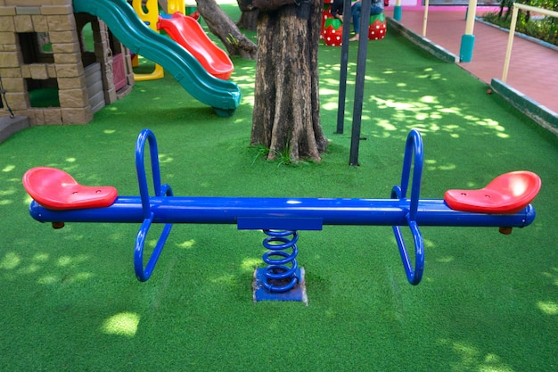 Teeterboard blu in bianco sul campo da giuoco dei bambini in giardino