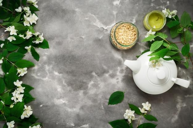 Teiera bianca, tisana secca, fiore di gelsomino, distesi piatti in marmo bianco nero. insegna di web lungo del modello di vista superiore dell'ora del tè