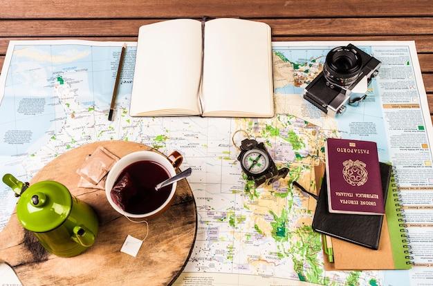 Teiera, bussola, passaporto, macchina fotografica e blocco appunti sulla mappa