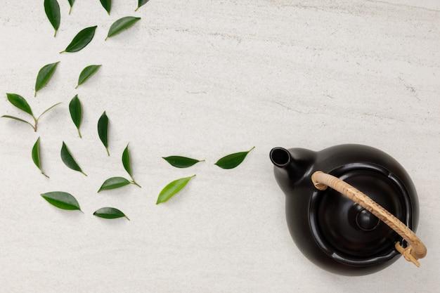 Teiera con le foglie di tè verdi organiche sulla disposizione piana piana creativa dello spazio vuoto dello scrittorio di pietra bianco