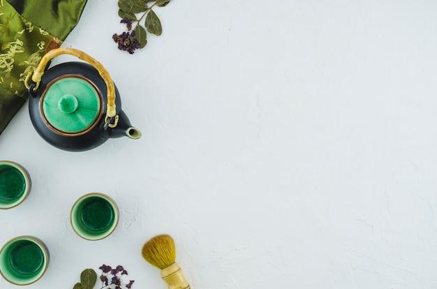 Teiera di erbe con tazze in ceramica e pennello isolato su sfondo bianco