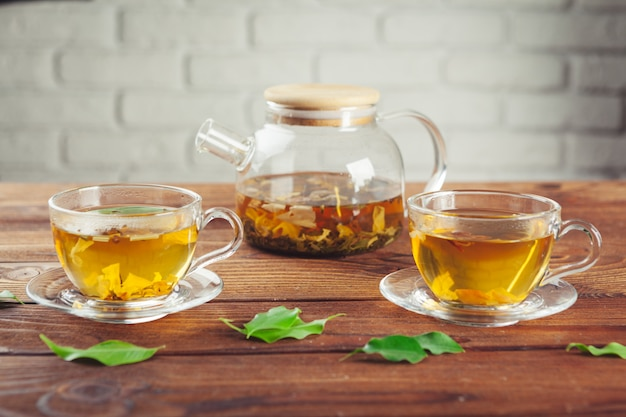 Teiera di vetro con la tazza di tè nero sulla tavola di legno