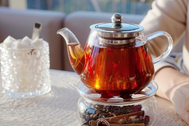 Teiera di vetro con tè al caffè. mani della donna con la tazza di tè su fondo