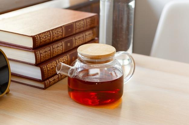 Teiera di vetro con tè nero sulla tavola di legno