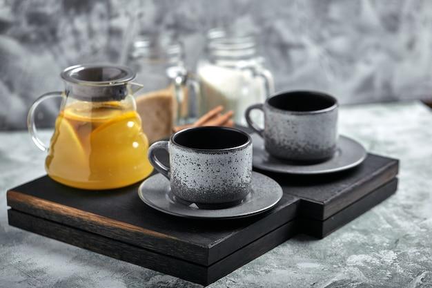 Teiera di vetro trasparente con tè e tazze di agrumi, set da tè su un tavolo di legno. primo piano, grigio, luce soffusa.