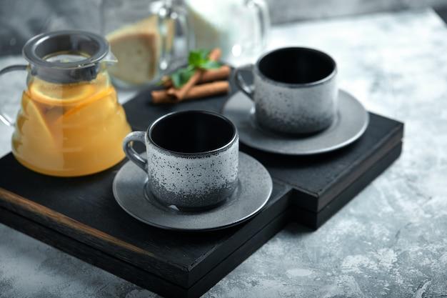 Teiera di vetro trasparente con tè e tazze di agrumi, set da tè su un tavolo di legno