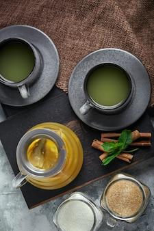 Teiera di vetro trasparente con tè e tazze di agrumi