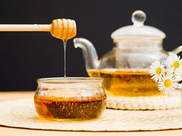 Teiera di vista frontale e merlo acquaiolo del miele sopra il barattolo