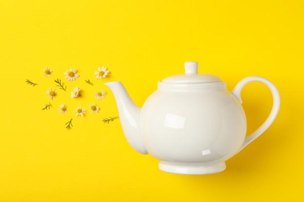 Teiera e camomille su giallo. tè alla camomilla
