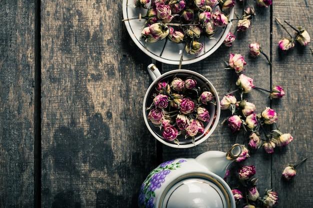 Teiera e tazza d'annata con i fiori di fioritura del tè su fondo di legno