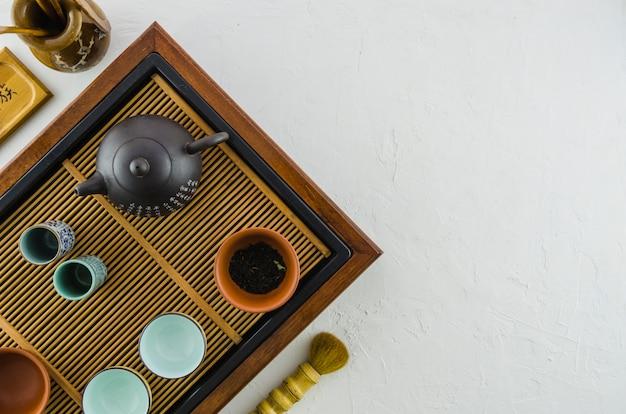 Teiera e tazza da the cinesi sul sottopentola di legno isolato su fondo bianco