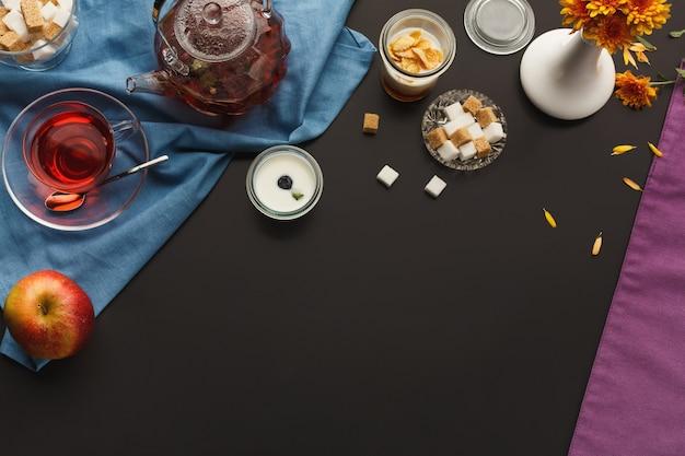 Teiera e tazza, dolci assortiti, spazio di copia