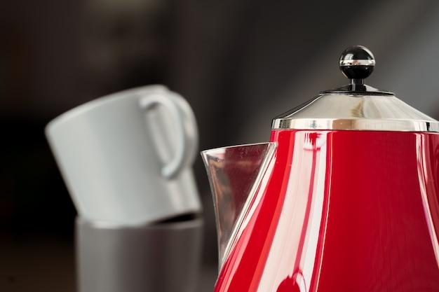 Teiera elettrica rossa di stile d'annata nell'interno della cucina