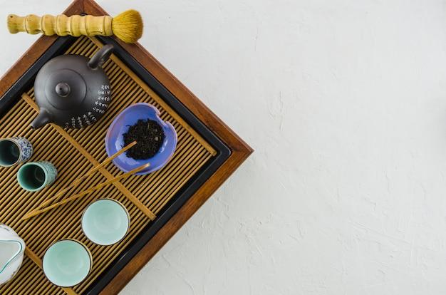 Teiera giapponese tradizionale; spazzola; erbe e tazze sul vassoio di legno su priorità bassa bianca