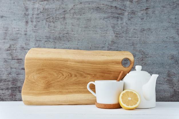 Teiera in ceramica, tazza bianca e limone
