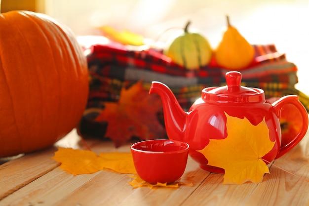 Teiera rossa con una tazza di tè, sciarpe a scacchi e foglia gialla d'autunno