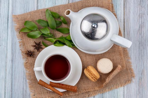 Teiera vista dall'alto con una tazza di tè alla cannella e amaretti su un tovagliolo beige su un tavolo grigio