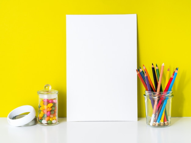 Tela bianca pulita del modello, matite colorate su fondo giallo luminoso. per creatività, disegno.