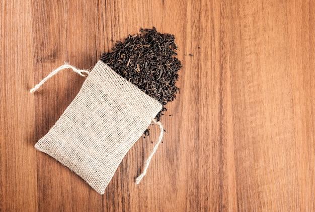 Tela da imballaggio d'annata con tè su fondo di legno
