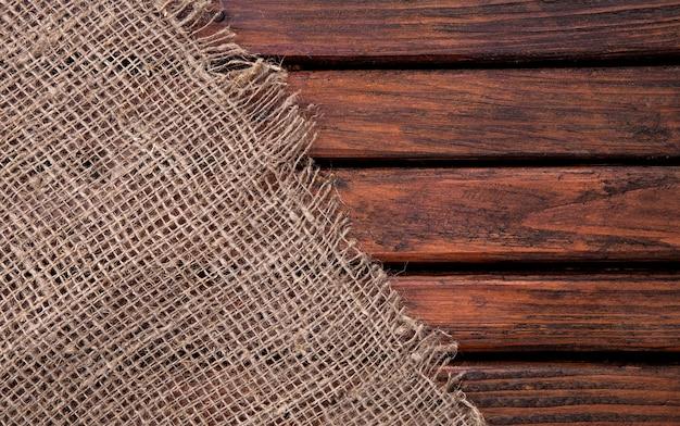 Tela di iuta della tela da imballaggio che licenzia su fondo di legno scuro