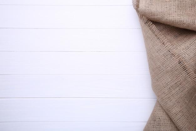 Tela di sacco naturale su fondo di legno bianco. tela su tavola di legno bianca