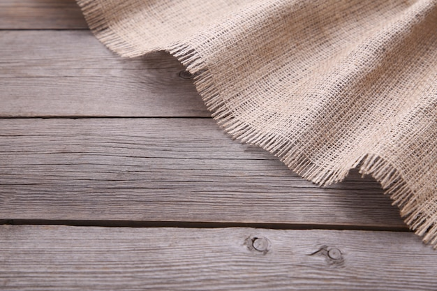 Tela di sacco naturale su fondo di legno grigio. tela su tavola di legno grigia