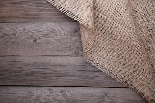 Tela di sacco naturale su fondo di legno grigio. tela sul tavolo di legno grigio