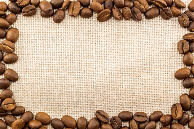 Tela di tela di sacco e chicchi di caffè disposti intorno