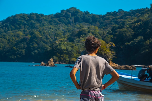 Tela, honduras: un bambino sulla spiaggia di puerto caribe a punta de sal nel mar dei caraibi