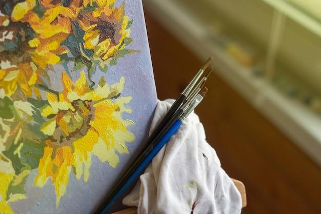 Tela, pittura, pennelli, spatola sdraiato sul tavolo.