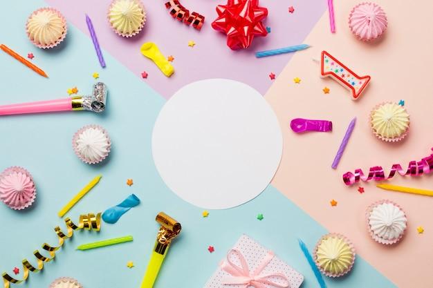 Telaio bianco cerchio vuoto circondato con aalaw; spruzzatori; filanti; palloncino e candele su sfondo colorato