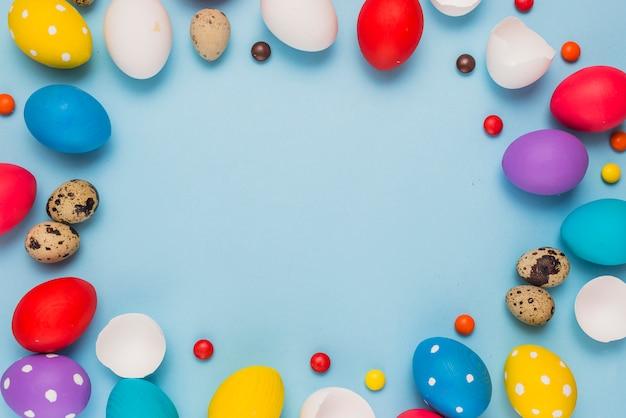 Telaio da uova di pasqua e caramelle sul tavolo blu