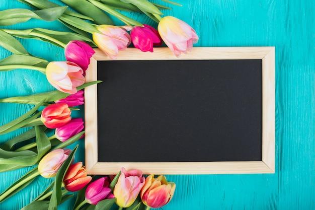 Telaio lavagna intorno bouquet di tulipani
