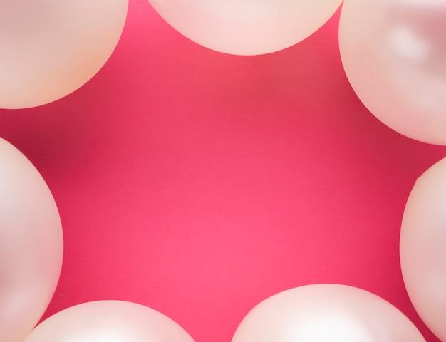 Telaio piatto laico con palloncini e sfondo rosa