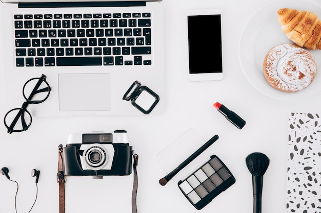 Telecamera; il computer portatile; cellulare; prodotto di cosmetici e pasticceria al forno sulla scrivania bianca