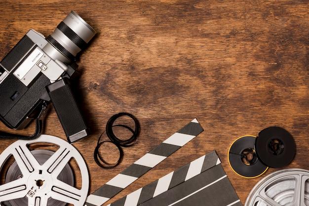 Telecamera videocamera con bobina di film; ciak; striscia di pellicola su fondo in legno