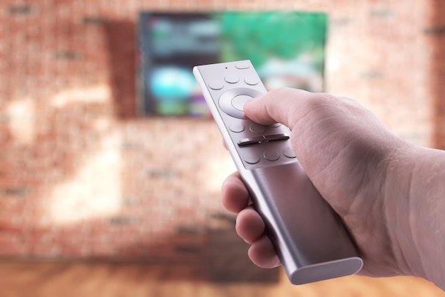 Telecomando della tv in primo piano delle mani
