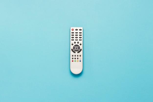 Telecomando grigio per tv su sfondo blu isolato. vista piana, vista dall'alto.