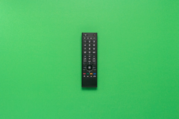 Telecomando nero su sfondo verde. il concetto di televisione, film, programmi tv, sport. vista piana, vista dall'alto.