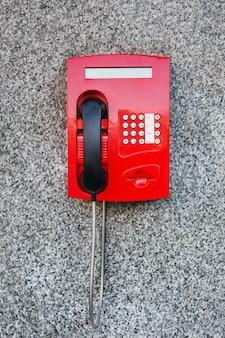Telefono a pagamento rosso sul muro.