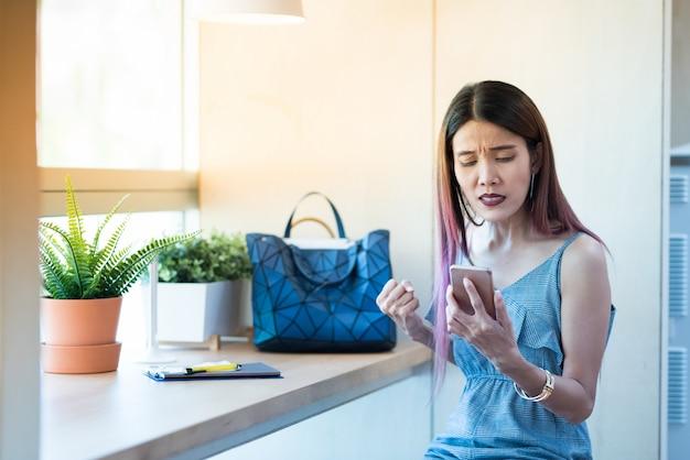 Telefono astuto astuto della tenuta asiatica della donna con successo felice sì mentre sedendosi nello sho del caffè